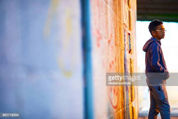 indonesian 12 years boy standing by the wall - 12 13 years stock pictures, royalty-free photos & images