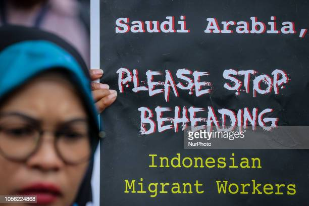 Indonesian activists from Migrant Care stands with a placard during a protest about the execution of Indonesian migrant worker Tuti Tursilawati in...