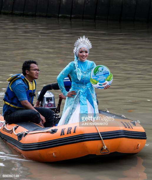 Indonesian activists parade in costume along the Kalimas river in Surabaya on March 22 2017 to help draw attention to World Water Day Recycling the...