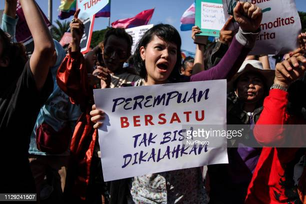 Indonesian activists were seen holding posters calling for equality for Indonesian women while taking action to mark International Women's Day in...