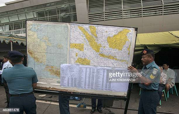 Indonesian Air Force officials carry map to show journalists the search area for the missing Malaysian air carrier AirAsia flight QZ8501 at the...