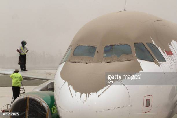Indonesian airport personnel inspect volcanic ash covered planes and the airport of Yogyakarta about 200 kilometers west of the Mount Kelud volcano...
