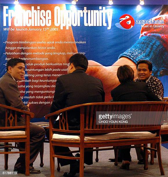 Indonesian and Chinese investors/franchisors talk in front of a billboard for the Franchise business opportunity Indonesia in Jakarta's Convention...