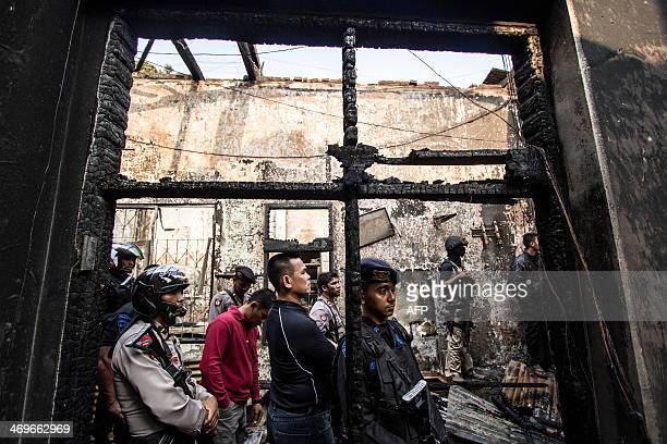 Indonesian antiriot policemen stand guard at the Lhokseumawe prison after a riot in Lhokseumawe on February 16 2014 At least three inmates were...
