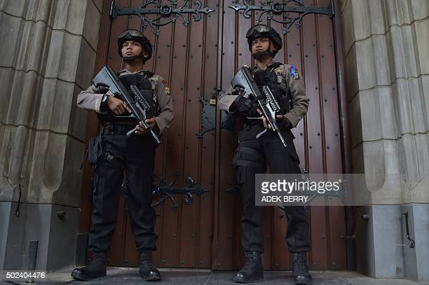 Indonesian antiterror and bomb police stand guard outside a cathedral during a security check ahead of a mass service on Christmas eve in Jakarta on...