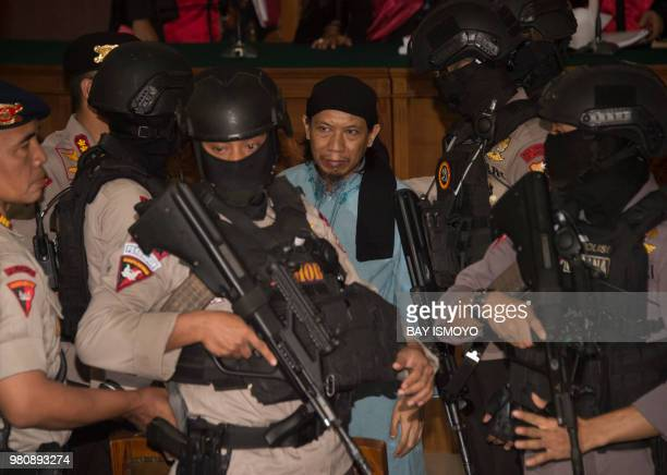Indonesian antiterror police officers escort Aman Abdurrahman who masterminded a 2016 gun and suicide attack in the capital Jakarta that left four...