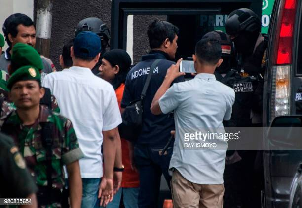 Indonesian antiterror police officers escort Aman Abdurrahman who is suspected of masterminding a 2016 gun and suicide attack in the capital Jakarta...