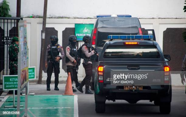 Indonesian antiterror police officers secure the area before escorting Aman Abdurrahman who is suspected of masterminding a 2016 gun and suicide...