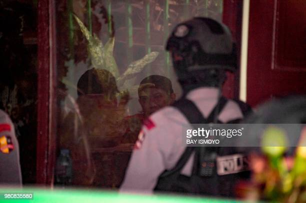 Indonesian antiterror police officers secure the detention room before Aman Abdurrahman who is suspected of masterminding a 2016 gun and suicide...
