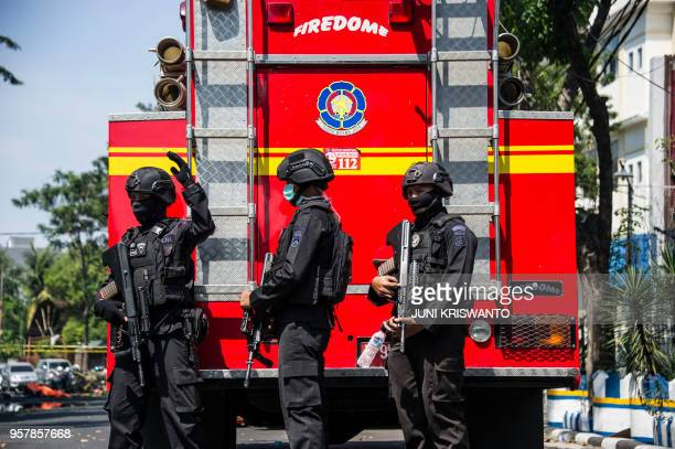 Indonesian antiterror policemen secure the site following a suicide bomb outside a church in Surabaya on May 13 2018 A wave of blasts including a...