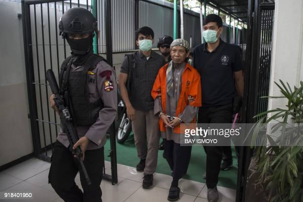 Indonesian armed police escort Indonesian radical cleric Aman Abdurrahman as he arrives at the South Jakarta court in Jakarta on February 15 for his...