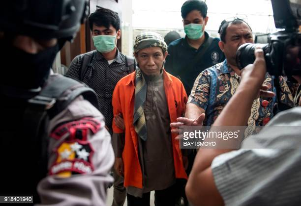 Indonesian armed police escort Indonesian radical cleric Aman Abdurrahman into the South Jakarta courtroom in Jakarta on February 15 during his first...