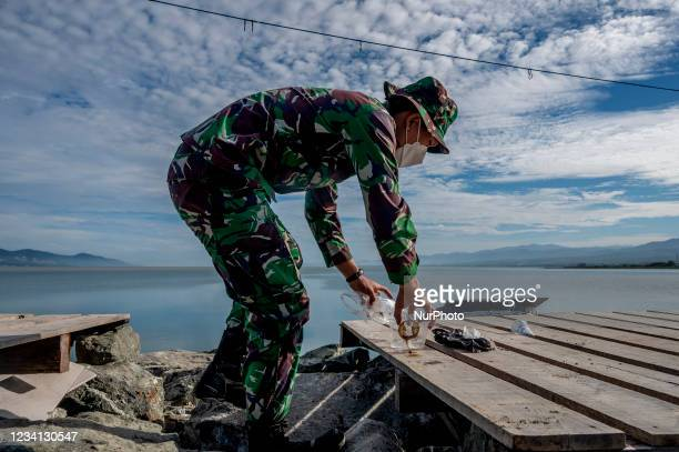 Indonesian Army soldier pick up plastic waste scattered in the Talise Beach area, Palu, Central Sulawesi Province, Indonesia on July 23, 2021. The...