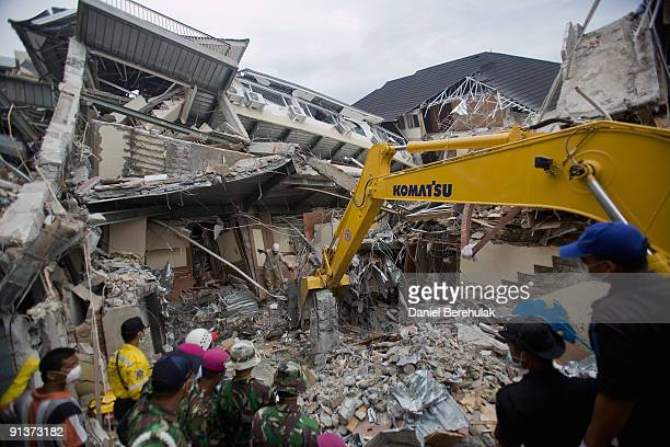 Indonesian army workers remove debris as they attempt to free a dead body from rubble at the Ambacang Hotel on October 3 2009 in Padang Indonesia An...