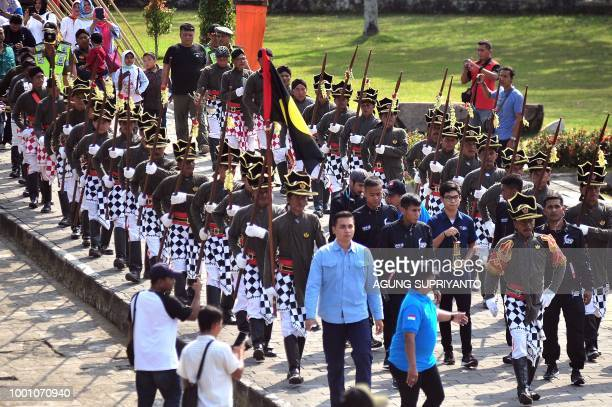 Indonesian Asian Games Organizing Committee officials along with Yogyakarta Keraton's security guards participate in a procession with the Asian...