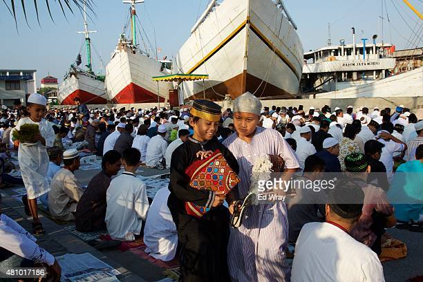 Indonesian boys get up to leave after attending Eid Al Fitr prayers at the Sunda Kelapa port on July 17 2015 in Jakarta Indonesia Hundreds of Ship...