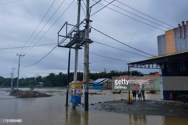 Indonesian boys look out over the neighborhood surrounded on three sides by flood water on March 21 2019 in Sentani Papua province Indonesia Over 100...