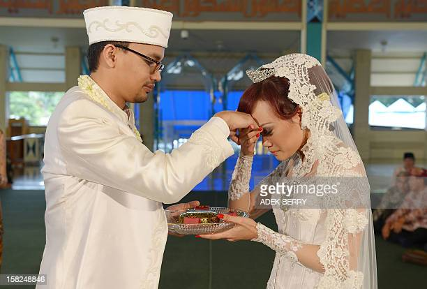 Indonesian bride Sitta Kusuma and groom Adam Afiezan take part in their Muslim wedding ceremony at a mosque in Jakarta on December 12 2012 Thousands...