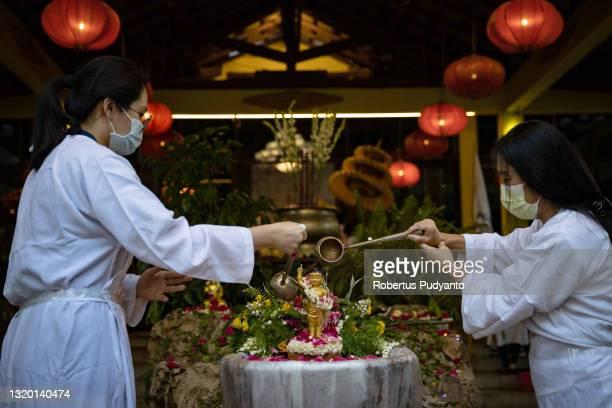 Indonesian Buddhists pour holy water on the Prince Siddhartha Gautama baby statue during the Vesak day 2565 BE ceremony at Maha Vihara Mojopahit...
