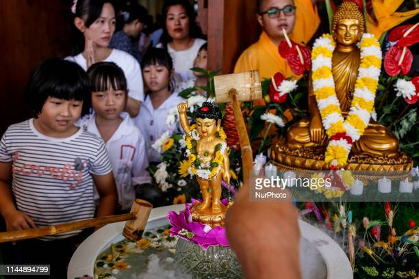 Indonesian Buddhists pour holy water over a Buddha statue during Vesak Day celebrations in Kuta, Bali, Indonesia on May 19 2019. Buddhists in Bali...