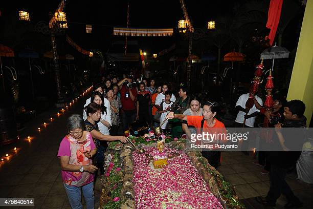 Indonesian Buddhists pour holy water over the baby Prince Siddhartha Gautama statue during the Vesak Day 2559 BE ceremony at Maha Vihara Mojopahit...