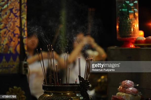 Indonesian Buddhists pray and burn incense sticks during the Vesak Day 2559 BE ceremony at Maha Vihara Mojopahit Trowulan on June 2 2015 in Mojokerto...