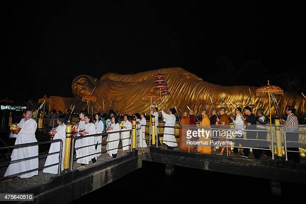 Indonesian Buddhists walk around big Buddha's Parinibbana statue during the Vesak Day 2559 BE ceremony at Maha Vihara Mojopahit Trowulan on June 2...