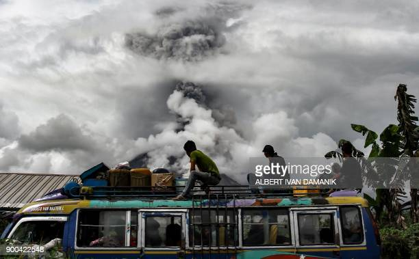 TOPSHOT Indonesian bus passengers watch as Mount Sinabung spews thick smoke in Karo North Sumatra on January 2 2018 Mount Sinabung roared back to...