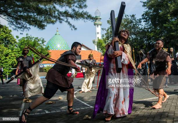 TOPSHOT Indonesian Catholics reenact the crucifixion of Jesus Christ as Christian devotees mark the holy week in Indonesia a predominantly Islamic...