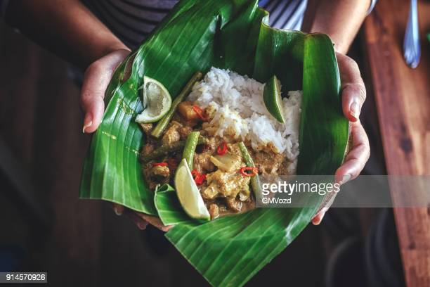 indonesian chicken curry dish with rice served on banana leaf - indonesian culture stock pictures, royalty-free photos & images