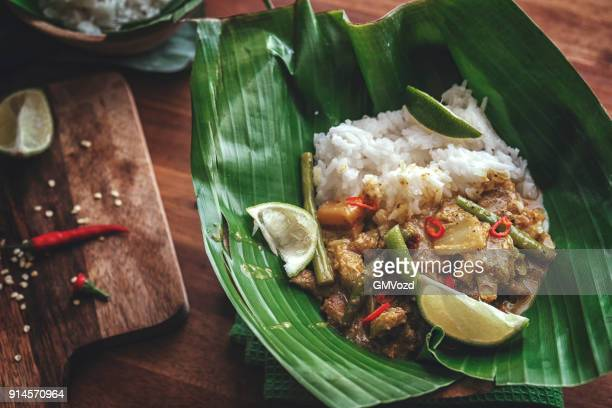 indonesian chicken curry dish with rice served on banana leaf - chicken masala stock photos and pictures