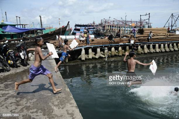 Indonesian children jump into the sea from a pier at the main fishing port of Muara Angke in Jakarta on February 5 using pieces of styrofoam as...