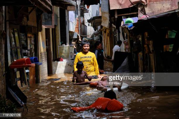 Indonesian children play in a flooded neighborhood on January 2, 2020 in Jakarta, Indonesia. Flooding caused by heavy rain left at least 17 people...