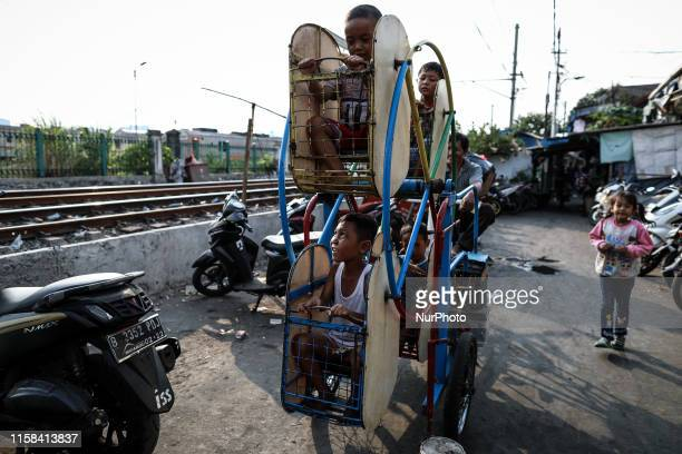 Indonesian children play on swings in Jakarta Indonesia July 29 2019 Indonesian government has set a target to reduce the poverty rate from 966...