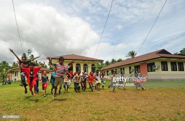 indonesian children running and jumping in school yard Banda Aceh Sumatra Indonesia