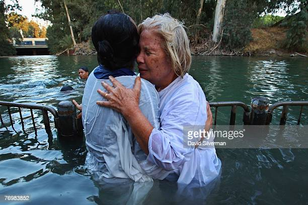 Indonesian Christian pilgrims embrace after they were baptised in the Jordan River on September 24 2007 at the Yardenit baptism site in northern...