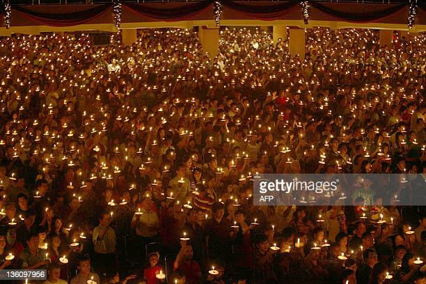 Indonesian Christians hold candles during a Christmas eve mass at the Bethany Church in Surabaya city in East Java province on December 24 2001 AFP...