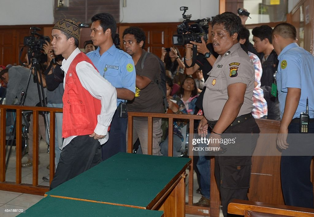 Indonesian cleaner Agun Iskandar (L-in white and red), one of five cleaners charged over allegations of sexual assault, arrives at the courtroom prior to his trial in Jakarta on August 26, 2014. Five cleaners were to go on trial this week over allegations of sexual assault at one of Indonesia's most prestigious international schools, the first cases in a long-running scandal to go to court.