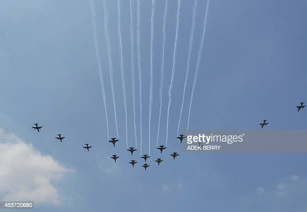 Indonesian combat aircraft F16 and Hawk of the US M50 of South Korea and Sukhoi of Russia fly over Indonesia's presidential palace during a ceremony...