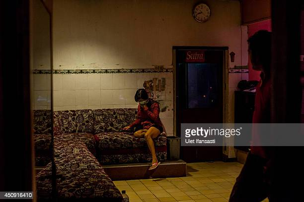 Indonesian commercial female sex worker masks her face inside a brothel as it's activity still runs after being closed by Surabaya's new Mayor at...