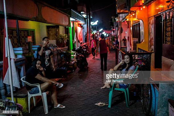 Indonesian commercial female sex workers are seen in front of a brothel as it still runs after being closed by Surabaya's Mayor at 'Jakak' redlight...
