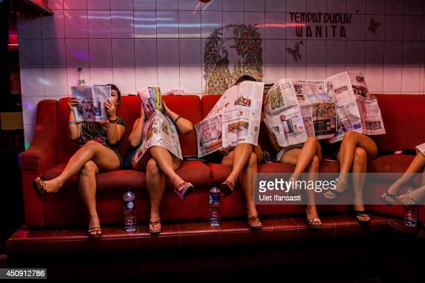 Indonesian commercial female sex workers cover their face sit lined up behind the glass inside a brothel as the activity still runs after being...