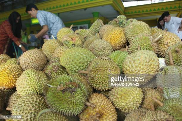 Indonesian customers buy durian fruit which sell between 14 to 7 USD at a stall in Medan on January 30 2019 Known as the king of fruits durians are...