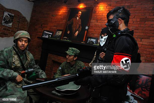 Indonesian customers come in World War II motif military uniforms one bearing a Nazi's swastika insignia while a portrait of Adolf Hitler hangs in...