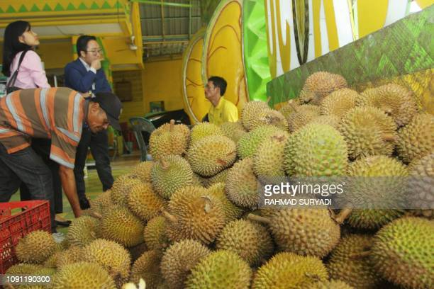 Indonesian customers sample durian fruits which sell between 14 to 7 USD at a stall in Medan on January 30 2019 Known as the king of fruits durians...