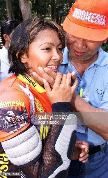 Indonesian cyclist Risa Suseanty is congratulated by Indonesian Assistant Chef de Mission Hussein Argasasmita after she won gold in the women's...