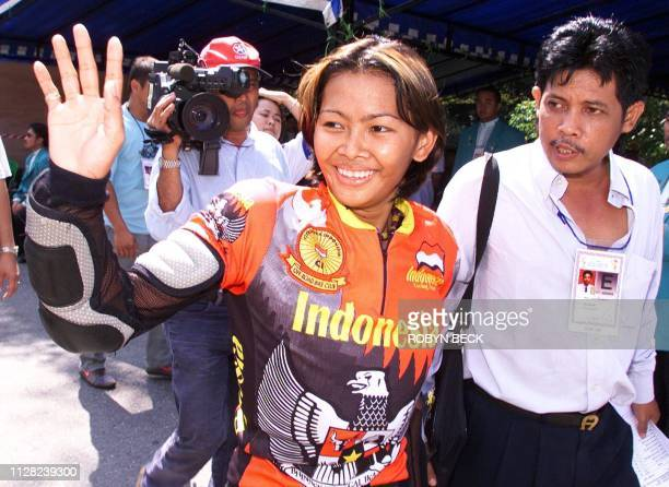 Indonesian cyclist Risa Suseanty waves after winning gold in the women's downhill mountain biking final at the 20th Southeast Asian Games in the...