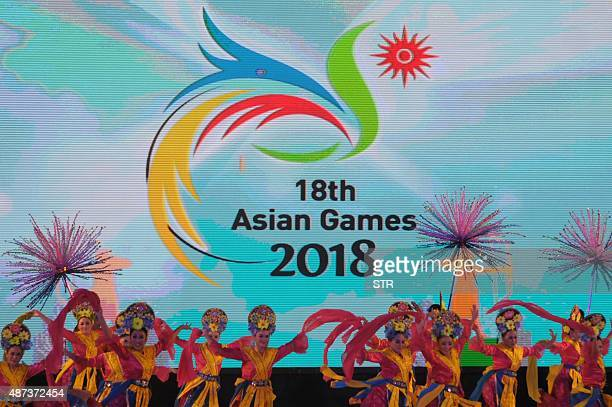 Indonesian dancers perform as the logo of the 2018 Asian Games appears in the background during a ceremony in Jakarta on September 9 2015 Indonesia...