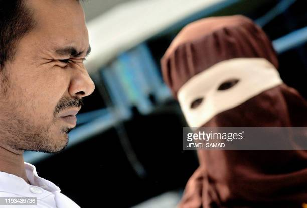 Indonesian Darkay grimaces in pain as he is caned in public by an ''algojo'' or veiled lawenforcement official after he was found guilty of gambling...