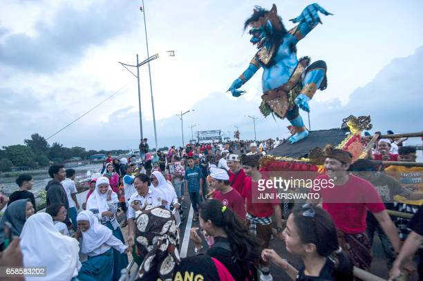 Indonesian devotees parade with effigies known as OgohOgoh to celebrate the festival of Nyepi 'Day of Silence' in Surabaya on March 27 2017 / AFP...